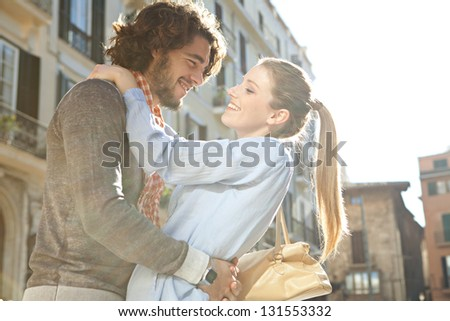 Profile view of an attractive couple hugging and being playful while having fun on vacation, with the sun rays filtering through. - stock photo