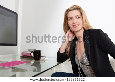 Profile view of an attractive professional woman working at her home office desk, using a desktop computer and being thoughtful.