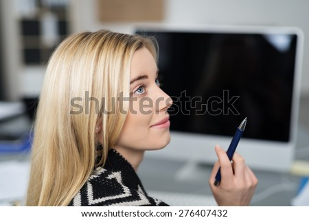 Profile view of an attractive young businesswoman looking up with a smile with her pen in her hand and an attentive expression as she looks at a work colleague