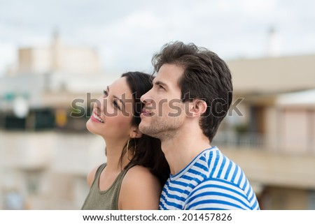 Profile view of an attractive young couple standing close together watching something up in the sky - stock photo