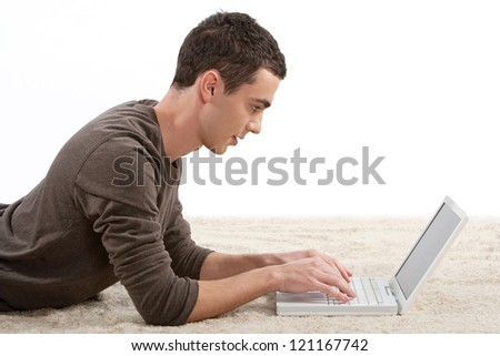 Profile view of an attractive young man using a laptop computer while laying down on a furry carpet at home.