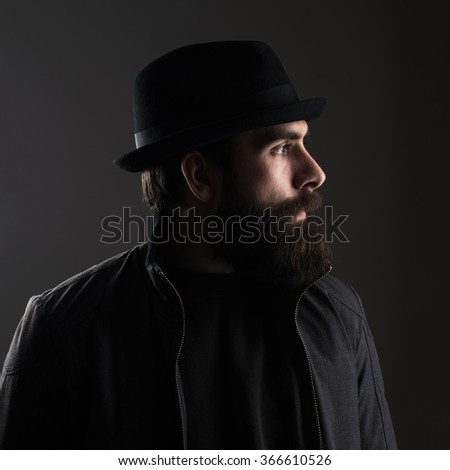 Profile view of bearded man wearing hat looking away. Low key dark shadow portrait over black background. - stock photo