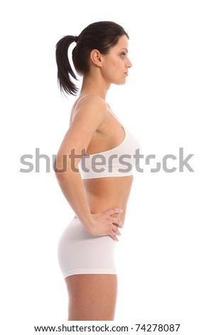 Profile view of beautiful healthy young woman wearing white sports underwear, standing against white background showing off fit body. - stock photo