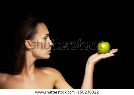 Profile view of beautiful woman holding green apple in her palm. Healthy caucasian woman with apple on black background. - stock photo