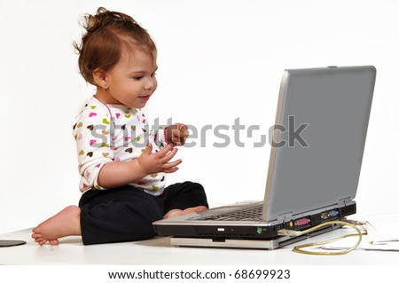 Profile view of cute toddler sitting on top of a desk, looking attentively at laptop display and smiling. - stock photo