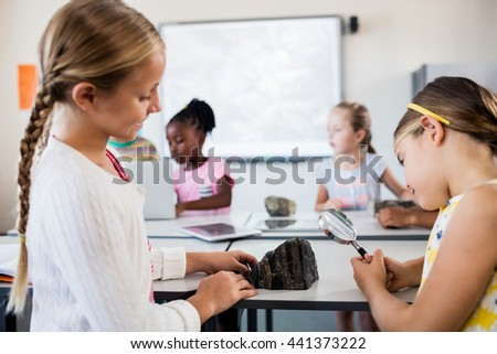 Profile view of girls looking at rock with magnifying glass in classroom - stock photo