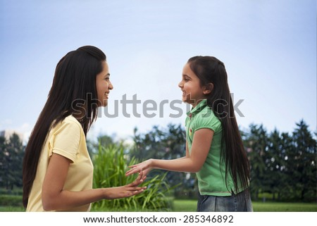 Profile view of happy mother and daughter playing over white background - stock photo