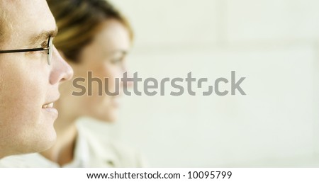 profile view of man and woman standing looking in same direction in front of office building. - stock photo