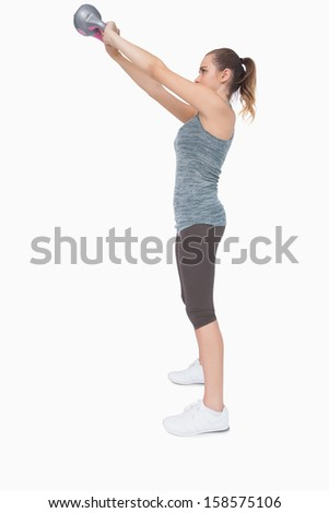 Profile view of pony tailed woman training with a kettle bell on white screen