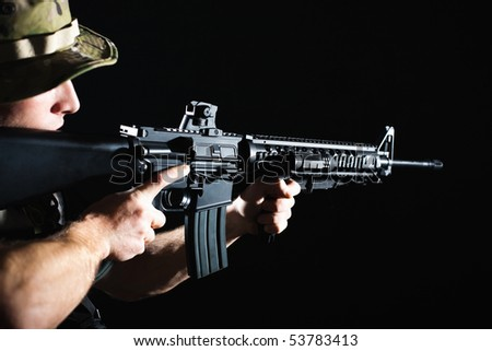 Profile view of soldier shooting with M16 assault rifle.