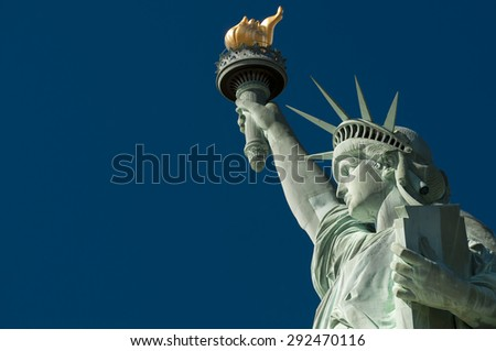 Profile view of the Statue of Liberty holding her torch against clear bright blue sky - stock photo
