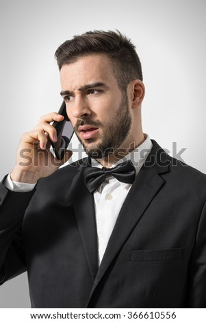 Profile view of upset angry wealthy man on the phone looking away. Portrait over gray studio background.  - stock photo
