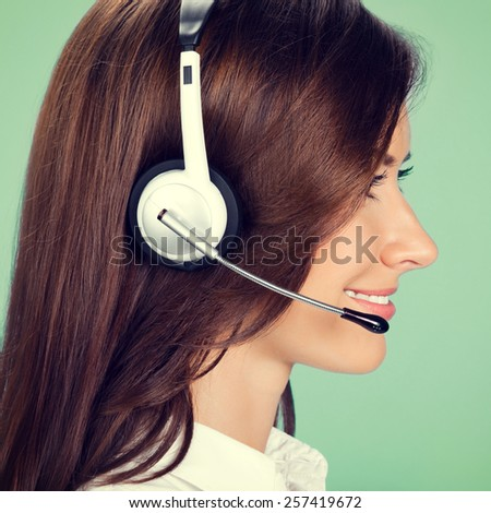 Profile view portrait of happy smiling cheerful customer support phone operator in headset, on green background - stock photo