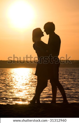 Profiles of romantic couple embracing each other on background of lake at sunset - stock photo