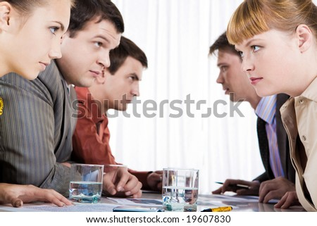 Profiles of serious employees sitting in two rows and looking at each other - stock photo