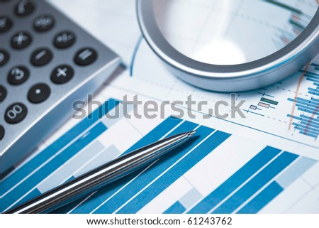 Profit bar chart, pen and calculator. Shallow DOF. Focus on the pen.