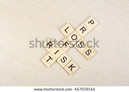Profit, loss and risk crossword blocks on table. Top view