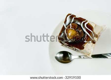 Profiterole covered with chocolate syrup on white plate - stock photo