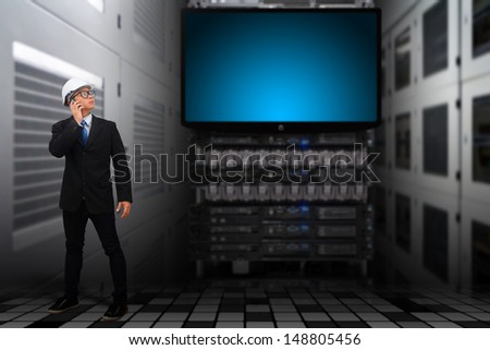 Programmer in data center room looking to LED monitor  - stock photo