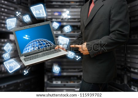 Programmer in data center room with Laptop for control the system : Elements of this image furnished by NASA - stock photo
