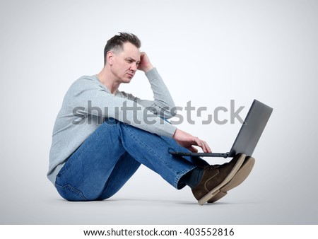 Programmer with laptop sitting on the floor - stock photo