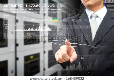 Programmers in data center room and touch on graph report  - stock photo