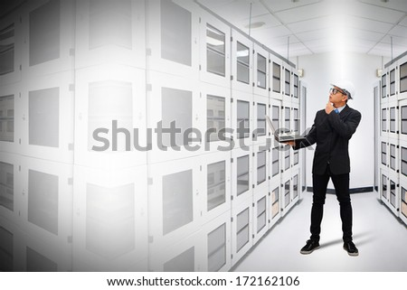 Programmers in data center room working with laptop  - stock photo