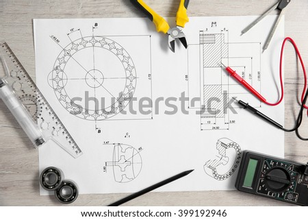 Project drawing and digital multimeter top view - stock photo