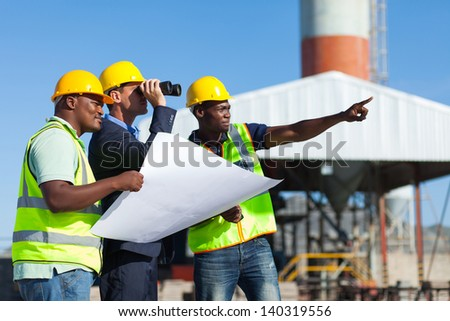 project manager visiting construction site with construction workers - stock photo