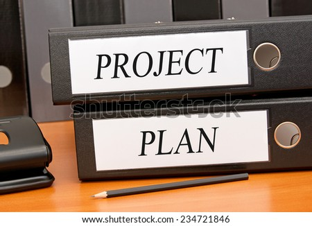 Project Plan - two binders on desk in the office - stock photo