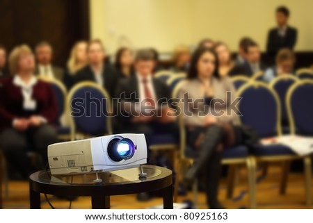 Projector on background of blur sitting people on yellow-blue chairs in bright conference hall - stock photo