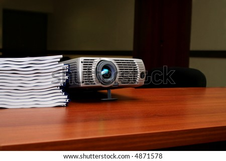 Projector with pile of books on the table #2 - stock photo