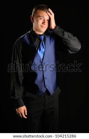 Prom Date Forgot Something. Teenager in a black tuxedo with his hand on his head as if he forgot something. - stock photo