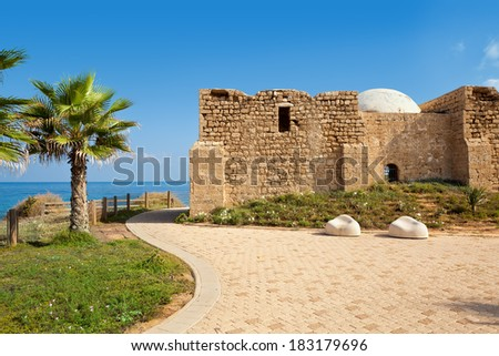 Promenade along Mediterranean sea coast with palms and ancient tomb of unknown shah in Ashkelon, Israel. - stock photo