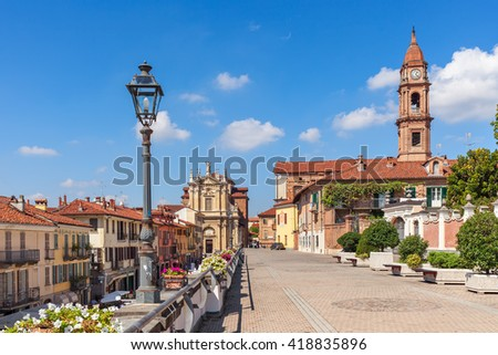 Promenade along old colorful houses, church and lampposts under blue sky in town of Bra in Piedmont, Northern Italy.