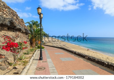 Promenade with tropical plants and flowers along a beach in Morro Jable holiday village, Fuerteventura, Canary Islands, Spain - stock photo