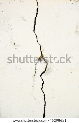Pronounced crack in a wall running vertically with extra textures - stock photo