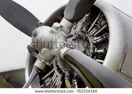 Propeller engine of classic metal plane, close up with grey sky.
