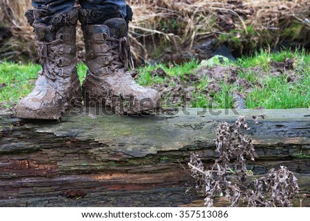 Proper childhood. Child in dirty stained boots - stock photo
