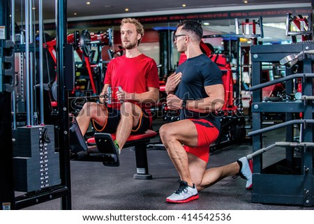 Proper training in the gym. Confident coach shows the customer how to do the training in the gym on the simulator. - stock photo