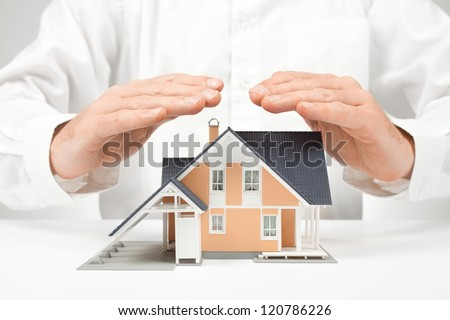 Property insurance concept - man protect model of the house. - stock photo