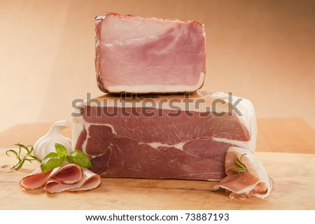 Prosciutto and ham piece with slices on wooden board. - stock photo