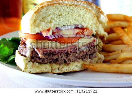 Prosciutto Burger - Prosciutto, beef burger, ham, mozzarella cheese, red onion and tomatoes with fries. - stock photo