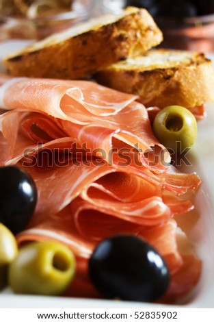 Prosciutto di Parma with olives and toasted bread - stock photo