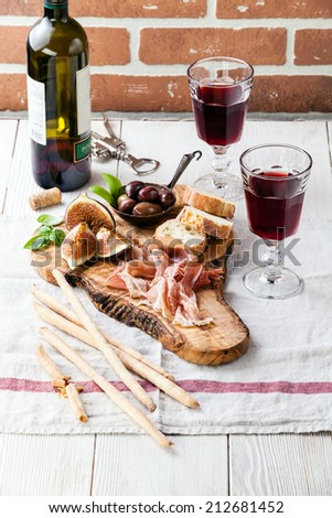 Prosciutto ham, Olives and red Wine on olive wood cutting board - stock photo