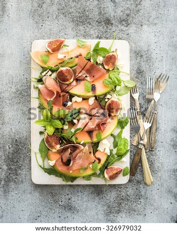 Prosciutto, melon, fig and soft cheese salad on a white serving board over grunge background, top view - stock photo