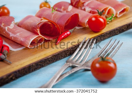 Prosciutto on  wooden table - stock photo