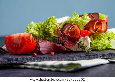 Prosciutto salad with cheese and tomatoes on a plate of natural slate - stock photo