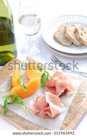 Prosciutto served with rockmelon, a common Italian antipasto with a glass of wine  - stock photo