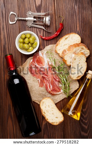 Prosciutto, wine, olives, parmesan and olive oil on wooden table. Top view